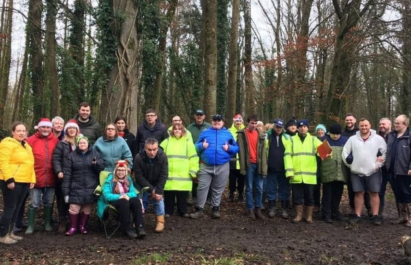 A group of Actif Woods Anglesey participants standing in a woodland smiling at the camera