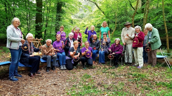 A group of people in woodland displaying their woodland crafts