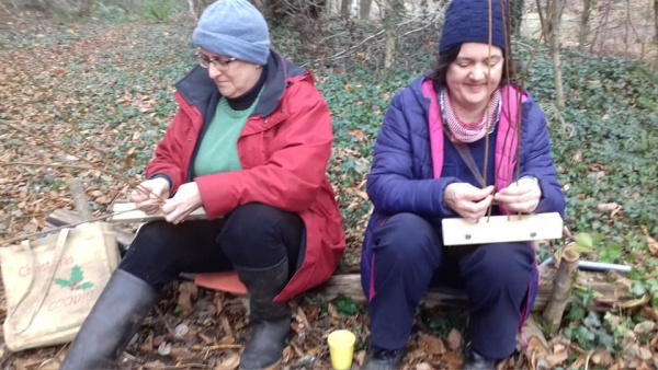 Two people sitting in a woodland doing woodland crafts